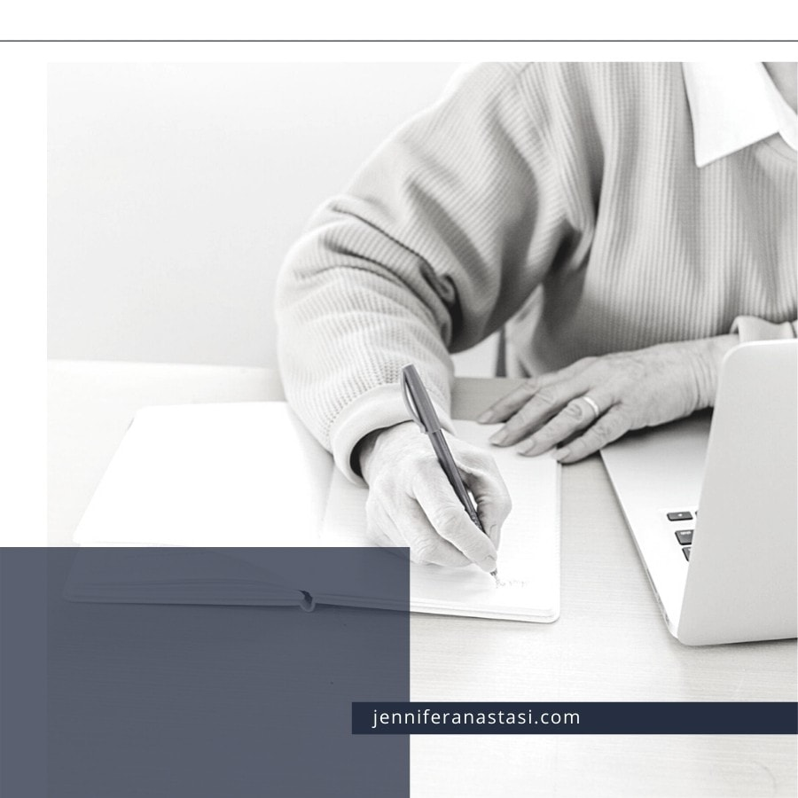 Woman writing at a desk with a laptop